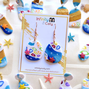 Polymer Clay Santorini Vibes Earring that displays the pristine golden sand, clear blue water and skies of Santorini - Teardrop shape with pink and red starfish