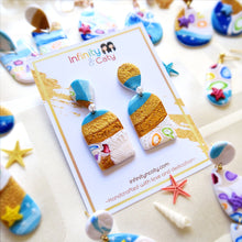 Load image into Gallery viewer, Polymer Clay Santorini Vibes Earring that displays the pristine golden sand, clear blue water and skies of Santorini - Arch shaped with teardrop stud