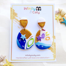 Load image into Gallery viewer, Polymer Clay Santorini Vibes Earring that displays the pristine golden sand, clear blue water and skies of Santorini - Teardrop dangle shape