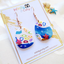 Load image into Gallery viewer, Polymer Clay Santorini Vibes Earring that displays the pristine golden sand, clear blue water and skies of Santorini - Teardrop shape with pink and red starfish