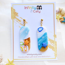 Load image into Gallery viewer, Handmade polymer clay earrings Singapore Santorini Vibes Earring that displays the pristine golden sand, clear blue water and skies of Santorini - Pill shape with orange and blue starfish