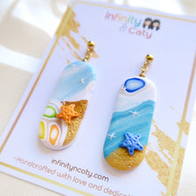 Load image into Gallery viewer, Polymer Clay Santorini Vibes Earring that displays the pristine golden sand, clear blue water and skies of Santorini - Pill shape with orange and blue starfish