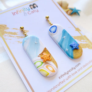 Polymer Clay Santorini Vibes Earring that displays the pristine golden sand, clear blue water and skies of Santorini - Pill shape with orange and blue starfish