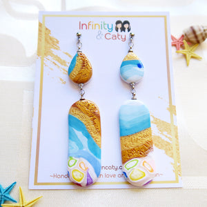 Polymer Clay Santorini Vibes Earring that displays the pristine golden sand, clear blue water and skies of Santorini