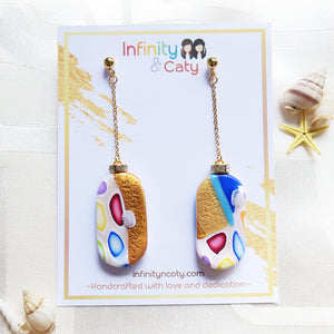 Polymer Clay Santorini Vibes Earring that displays the pristine golden sand, clear blue water and skies of Santorini double sided design