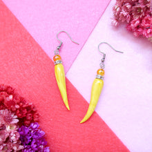Load image into Gallery viewer, Handmade yellow ivory shaped polymer clay earrings with crystal and bead embellishments on pink background