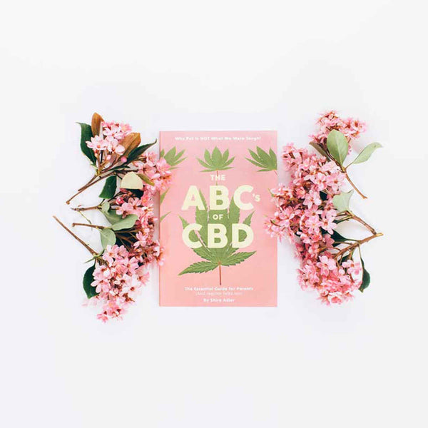 The ABC's of CBD book styled with pink flowers