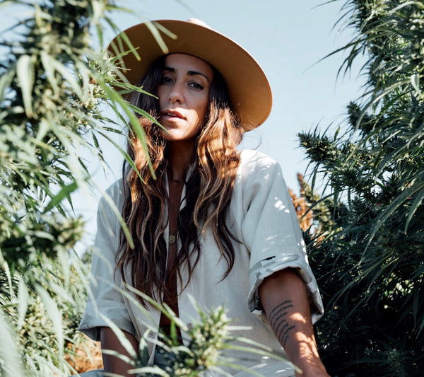 Lex Weinstein in Arraei Collective Hemp Coat standing in hemp field