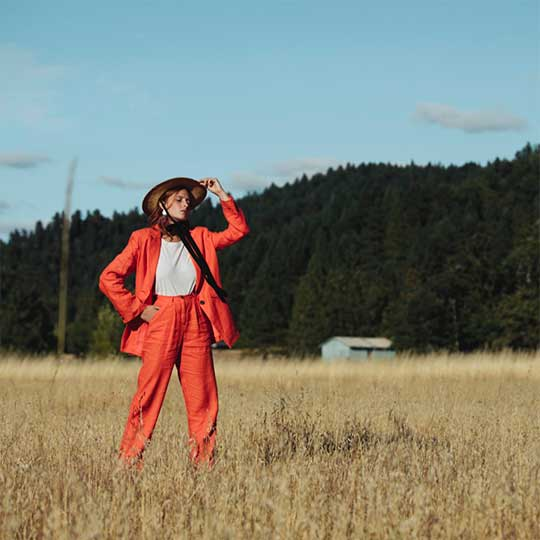 Model standing in field wearing orange hemp suit from Svn Space Print Issue shoot