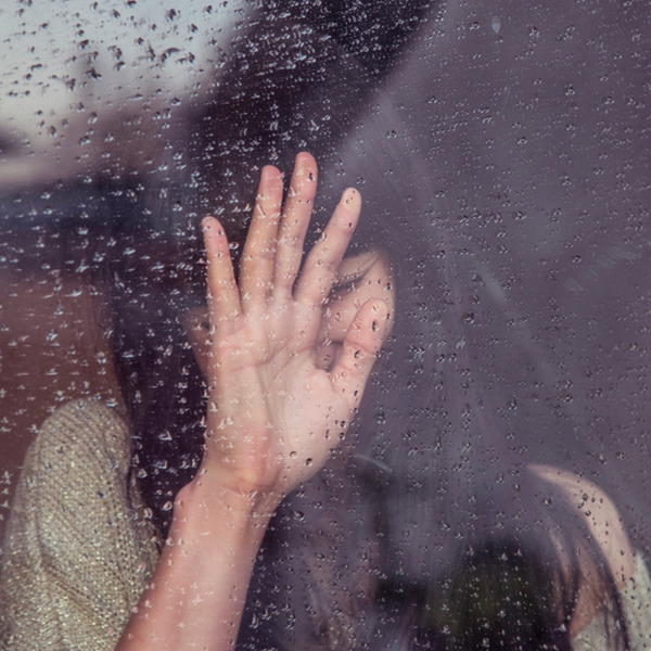 Girl leaning against window suffering from anxiety