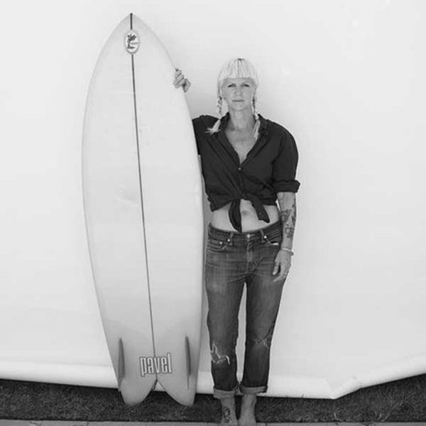 Heidi Zumbrun standing with her surfboard against a wall, photographed by Michael Beck