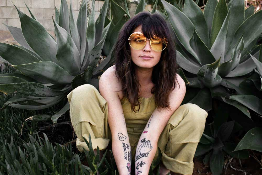 Lindsay Perry sitting down in hemp outfit against plants