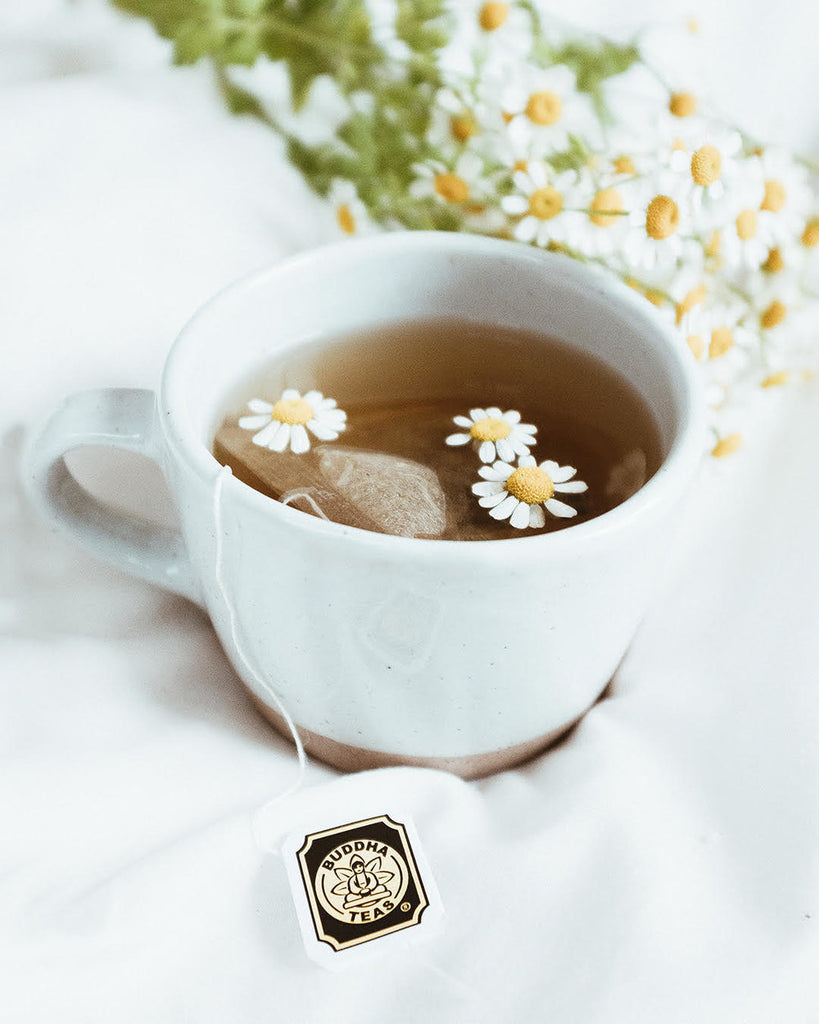 Buddha CBD Tea in cup with floating daisies by Cheyenne Arnold
