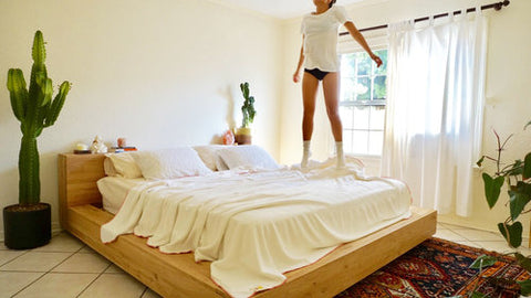 I Love Bad Hemp blanket and girl jumping on bed in hemp tee, undies, socks