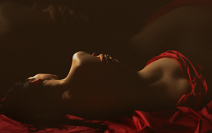 Girl laying on bed wrapped in red cloth