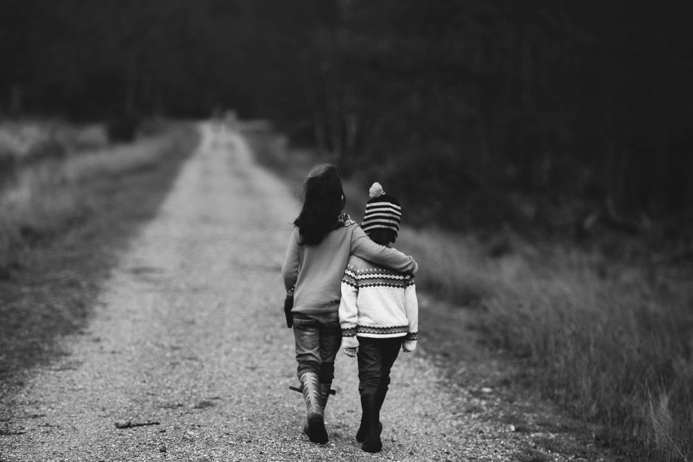 Two children with autism walking down a dirt road