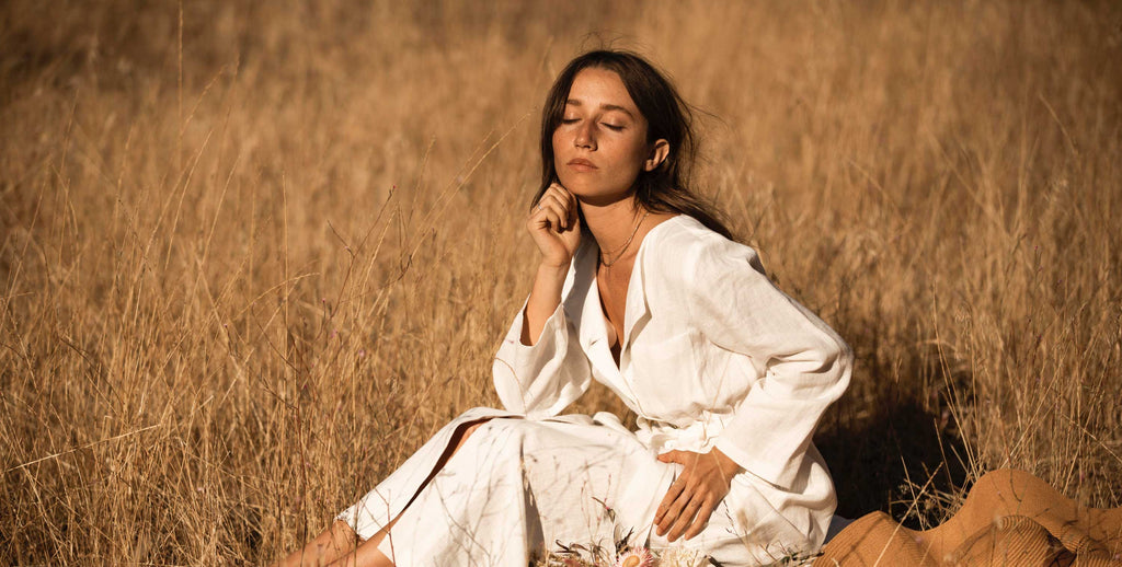 Girl sitting in field with white hemp dress on