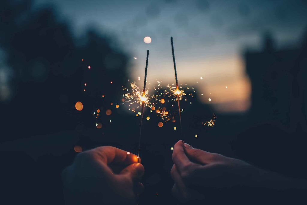 two hands holding sparklers close together at sunset