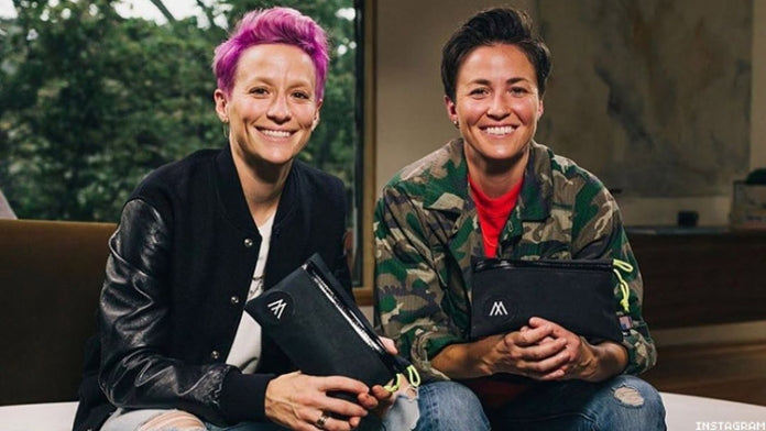 Megan and Rachael Rapinoe sitting next to each other and smiling