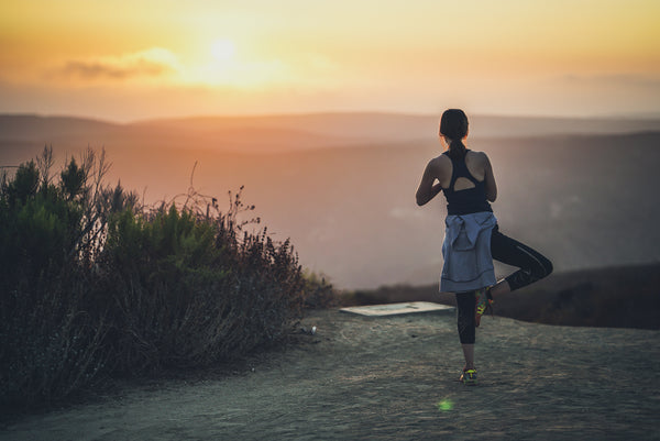 Girl stretching while watching sunset after jogging