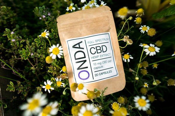 Onda CBD Oil Capsules 10mg styled shot in flowers by Svn Space.