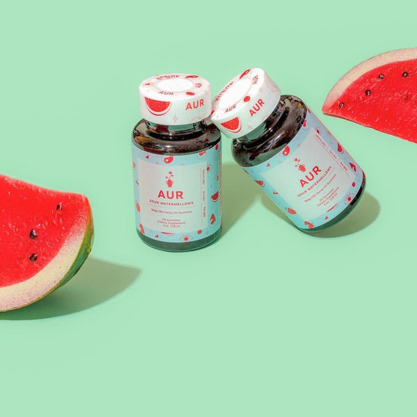 AUR Watermellow CBD Gummies with 5mg CBD styled shot of two bottles next to watermelons by Svn Space.