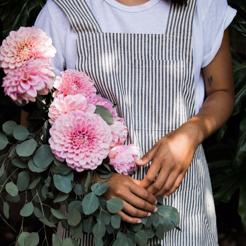 Girl foraging flowers wearing Hemp Apron Prairie Smock Cross-Back Indigo Stripe by Portland Apron Co, Svn Space.