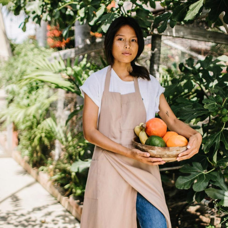 Girl glancing carrying fruit bowl wearing Hemp Apron Split Leg in Sand color by Portland Apron Co, Svn Space.