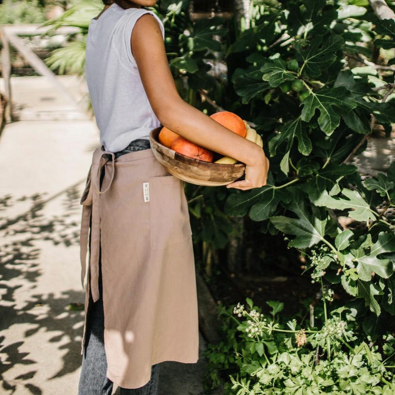 Girl foraging fruit wearing Hemp Apron Split Leg (Sand) by Portland Apron Co.