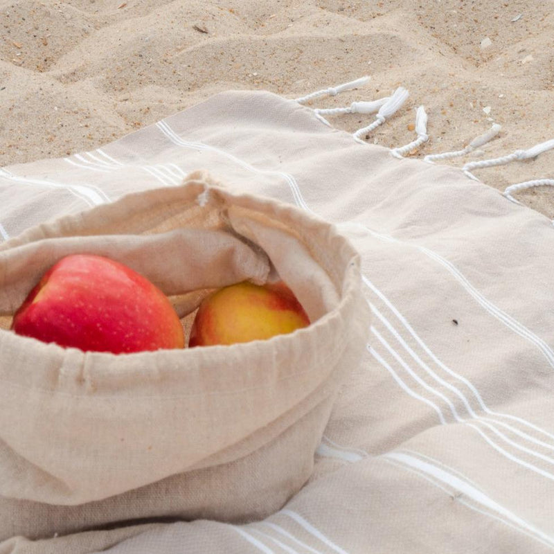 Sunshine Series apples and oranges inside bag on beach