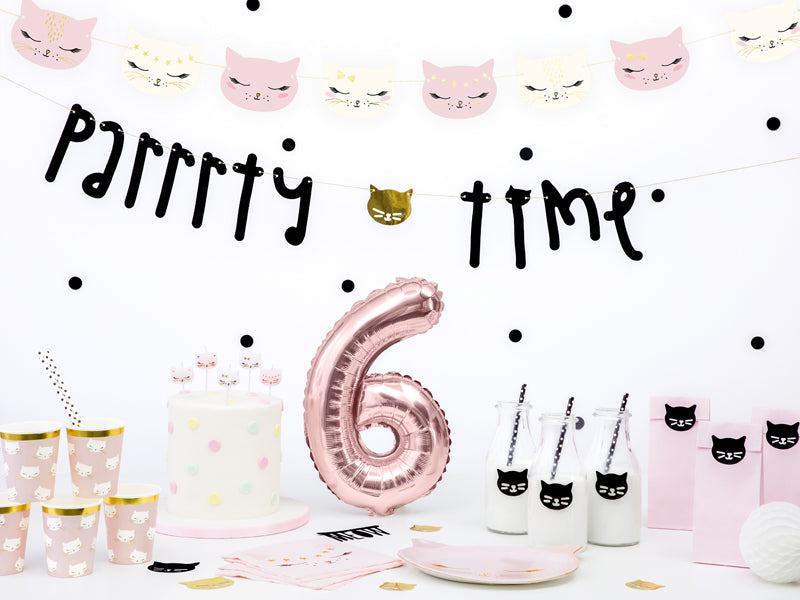 pink and gold cat party decorations with cat face banners, cups, plates and party bags