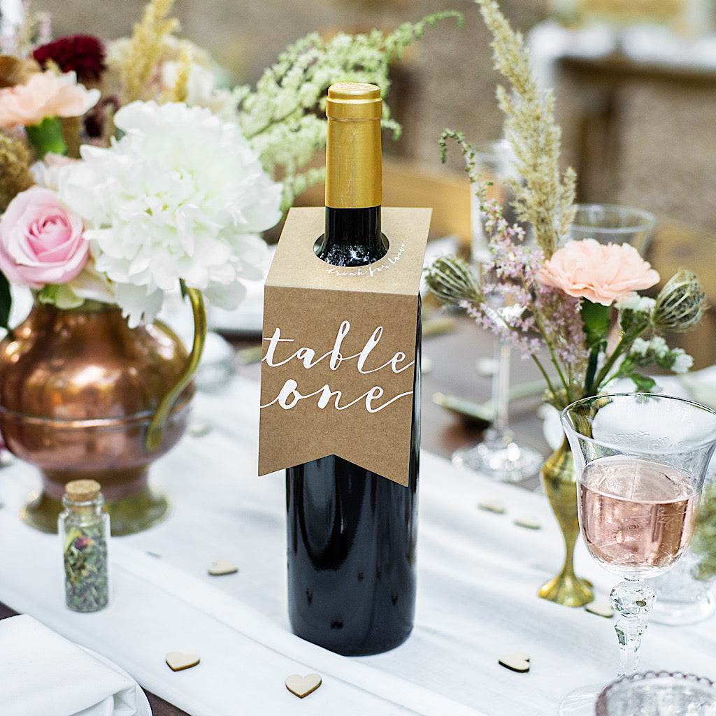 Kraft paper table number bottle hangers with the words printed table one in white