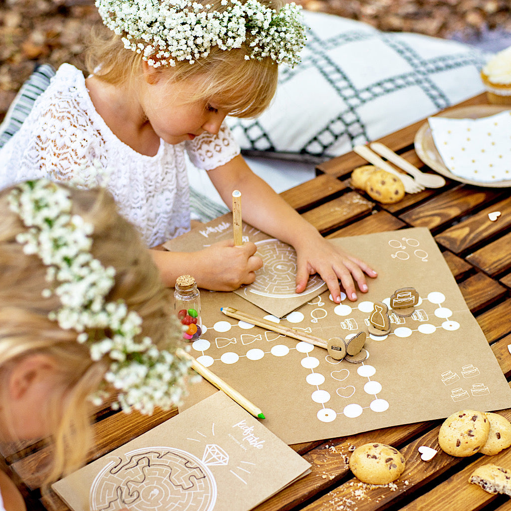 Childrens wedding activity games pack in kraft paper with wooden dice and 4 books with various games to play including maze, battle ships etc