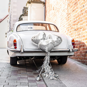 Wedding day car decoration kit with silver heart foil balloons, tassels and cans to decorate the back of the wedding car