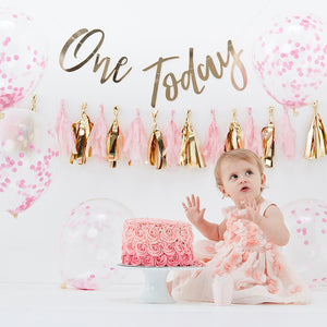 pink first birthday cake smash decorations kit. Includes one today gold banner, pink and gold tassle garland, pink confetti balloons and 1 gold foil party hat