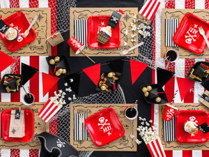 table decorations with square red plates and red cups with skull and bone white picture, brown and black illustration treasure map place mats. Black and white striped paper napkins in black and white with red triangle bunting. Pirate themed birthday party for girls and boys party or birthday parties from la di dah