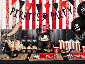 table decorations with square red plates and red cups with skull and bone white picture, brown and black illustration treasure map place mats. Black and white striped paper napkins in black and white with red and black triangle bunting. Black Pirate party hanging banner, pirate party bags in brown paper, sails in red and white cake toppers with black octopus legs. Pirate themed birthday party for girls and boys party or birthday parties from la di dah