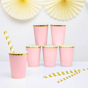 Pale pink paper party cups with gold scalloped edge detail.