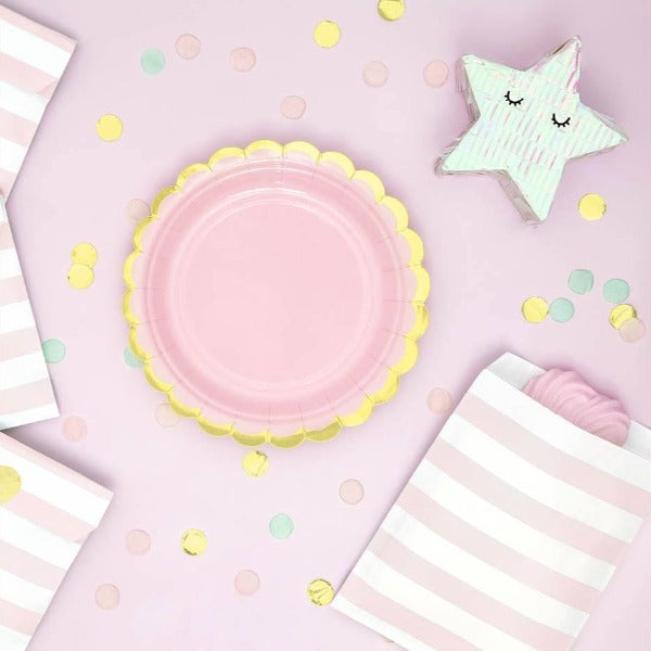 Pastel pink paper party plate with scalloped gold edge.