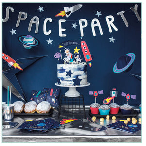 Space party styled image with garlands, cake topper, napkins, rocket shaped plates, space party cups.