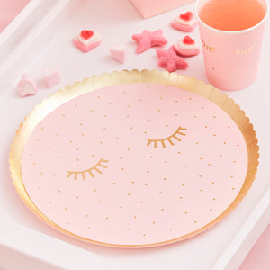 Pink pamper party with gold eyelash design party plates.