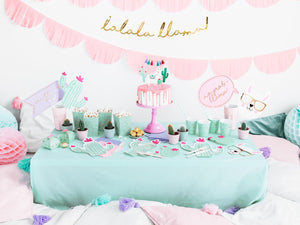 Llama party decorations with gold llama garland, pale pink scalloped garland, mint and gold party cups, mint popcorn boxes, cactus plates and cactus napkins.