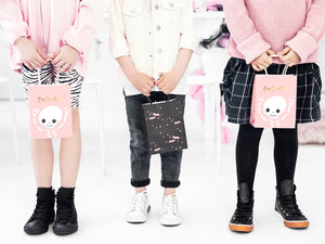 Three children holding halloween party bags. Black party bags with pale pink bats and pink and gold stars