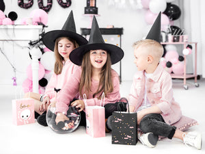 children celebrating halloween with witches hats and black and pink party bags.