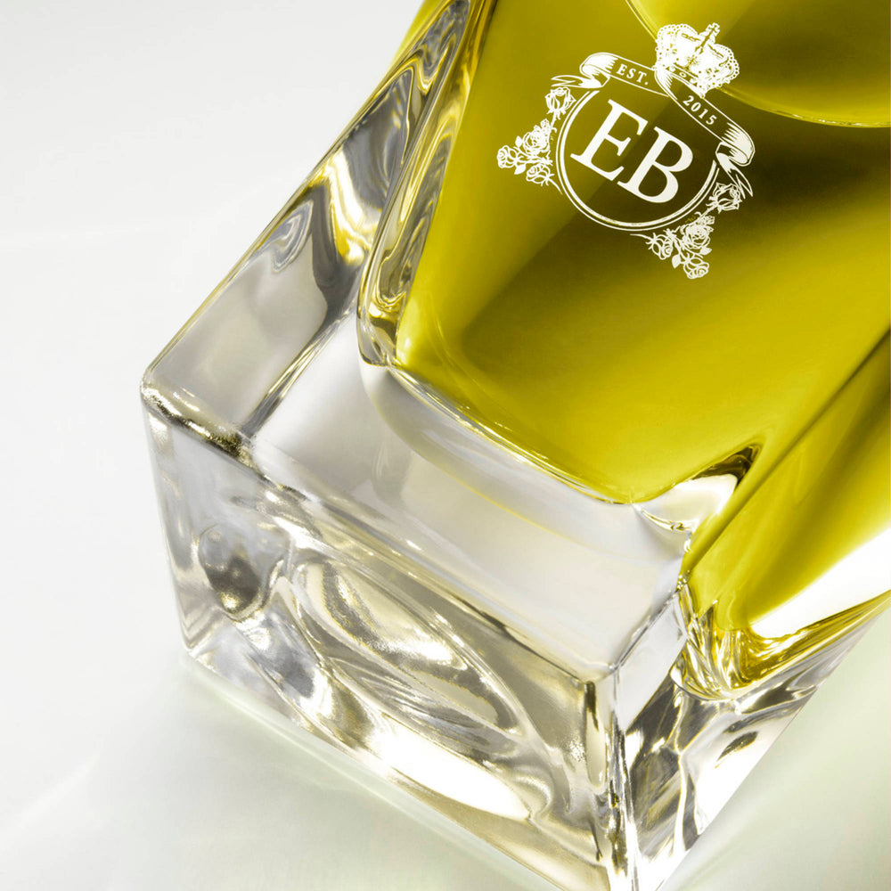 Detail of the bottom of the 100 ml bottle, with transparent glass and greenish perfum. Detail of logo with the EB initials in white ink. Apollo Hyacinth, a fragrance by Eric Butherbaugh.