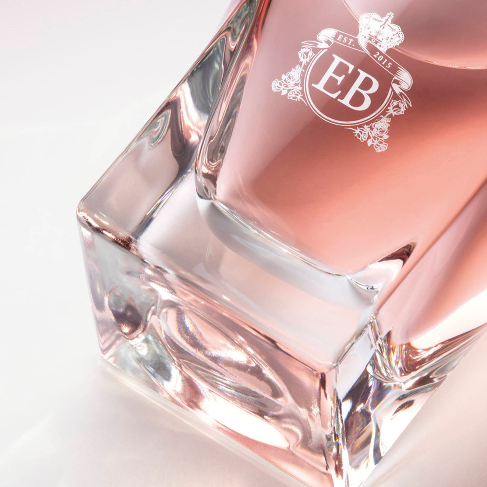 Detail of the bottom of the 100 ml bottle, with transparent glass and pinkish perfum. Detail of logo with the EB initials in white ink. Celestial Jasmine, a fragrance by Eric Butherbaugh.