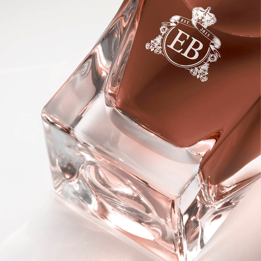 Detail of the bottom of the 100 ml bottle, with transparent glass and amber perfum. Detail of logo with the EB initials in white ink. 1947 Dalhia, a fragrance by Eric Butherbaugh.