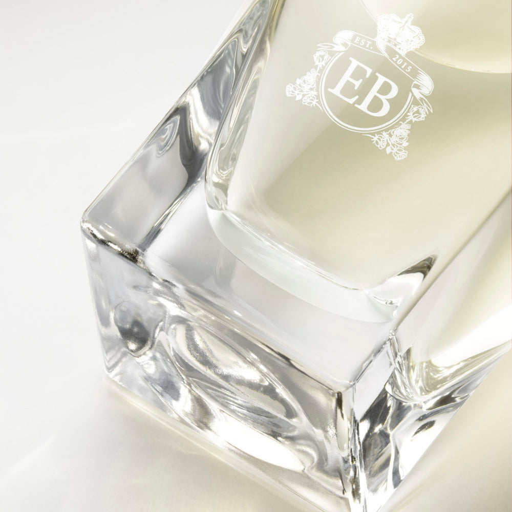 Detail of the bottom of the 100 ml bottle, with transparent glass and yellowish perfum. Detail of logo with the EB initials in white ink. Fabulous Magnolia, a fragrance by Eric Butherbaugh.