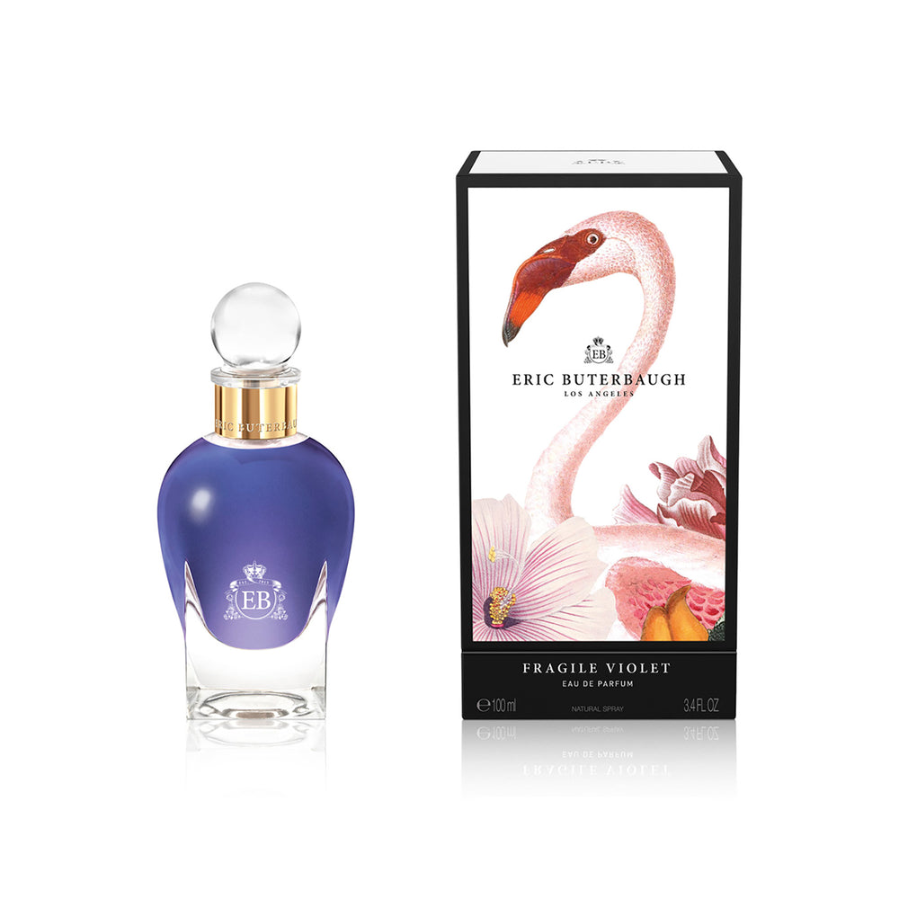 100 ml bottle, with transparent glass and violet perfum. Spherical cap with gold band. By his side the box, with pink flamingo and flowers illustration, within a black border. Fragile Violet, a fragrance by Eric Butherbaugh.
