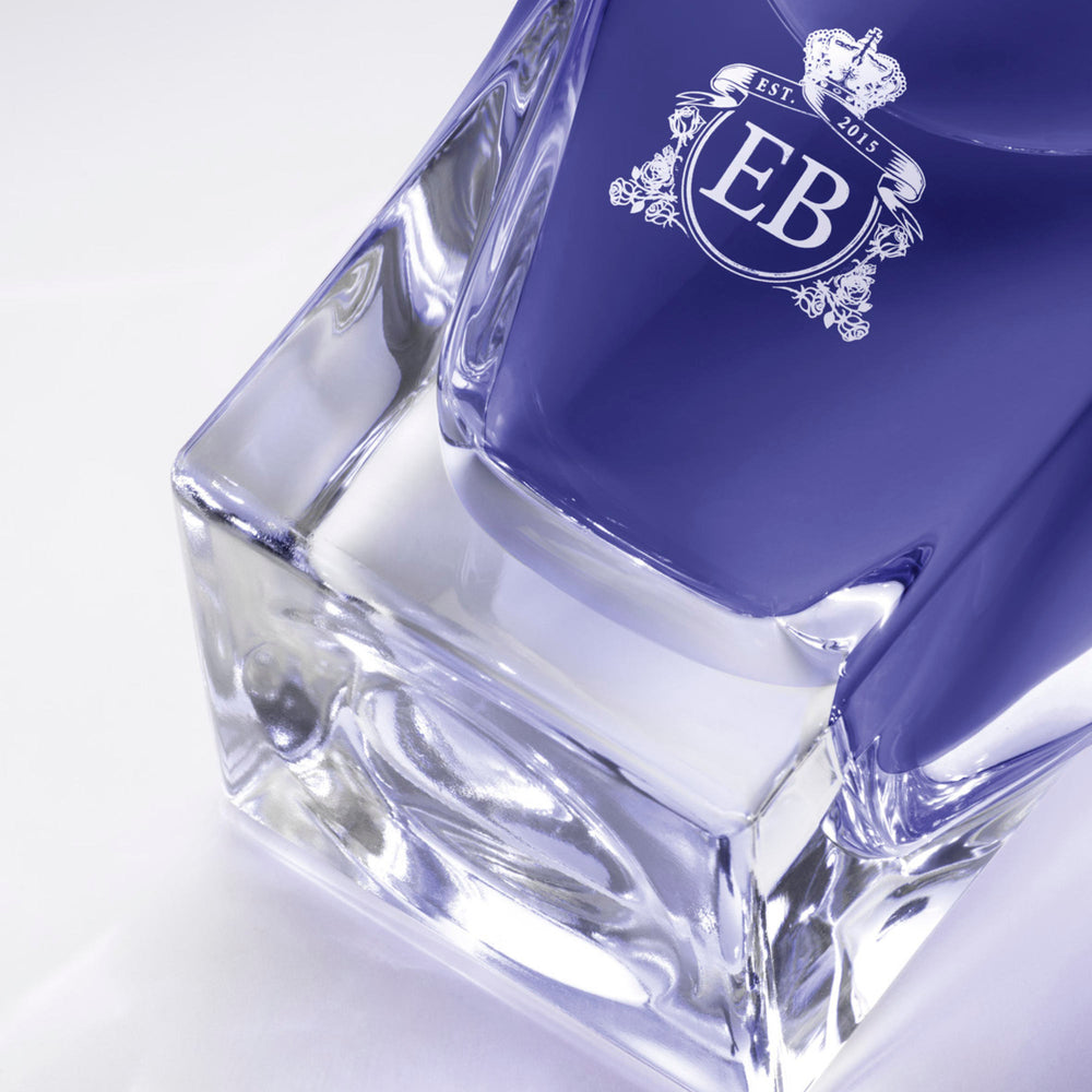 Detail of the bottom of the 100 ml bottle, with transparent glass and violet perfum. Detail of logo with the EB initials in white ink. Fragile Violet, a fragrance by Eric Butherbaugh.